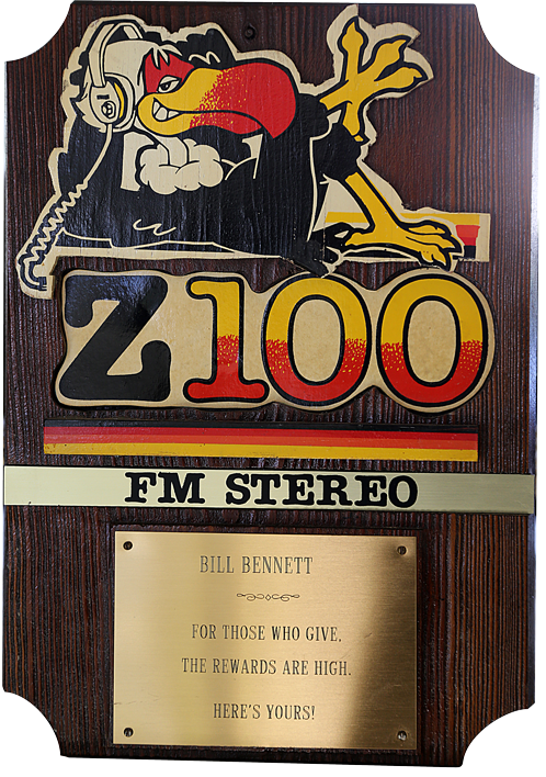 wooden plaque with a cutout of the Z100 buzzard and the Z100 logo. Inscription reads &lquo;For those who give the rewards are high. Here's yours&rquo;